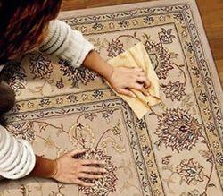 Женщина чистит ковер домашними средствами