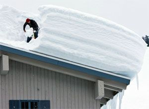 Мужчина убирает снег и сосульки с крыши