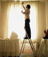 Женщина весит шторы