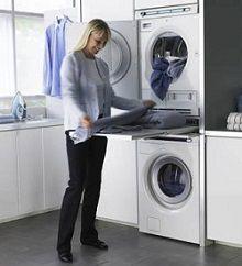 Женщина достает белье из сушильной машины